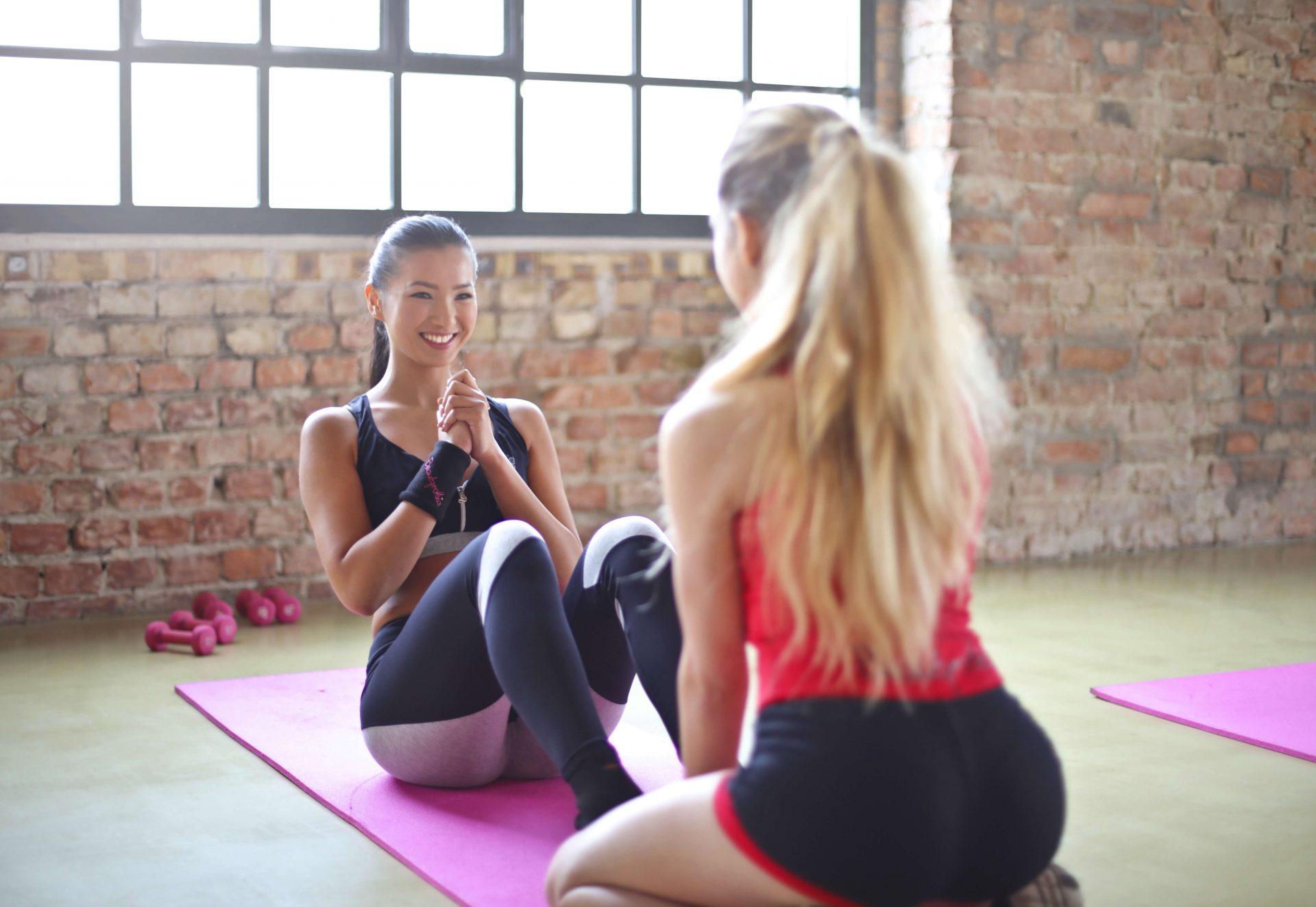 Uma mulher de cabelo preto fazendo abdominais sorrindo enquanto outra mulher de cabelos loiros está de costas ajudando-a segurando seus pés.